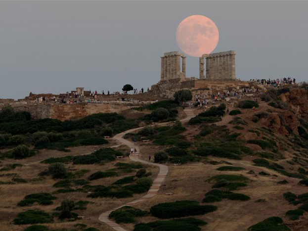 View of full moon rising over ancient Temple of Poseidon in Greece