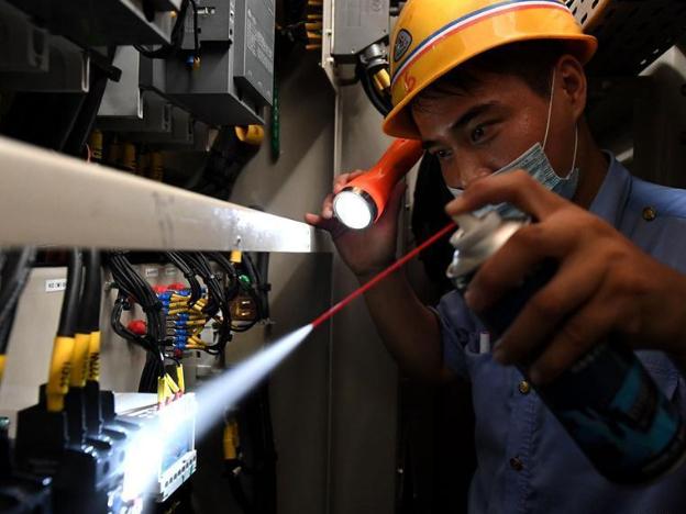 Maintenance workers busy repairing trains at workshop in Henan