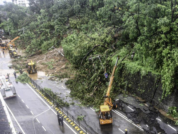 Firefighters clear road after rain-triggered landslide in Mumbai, India