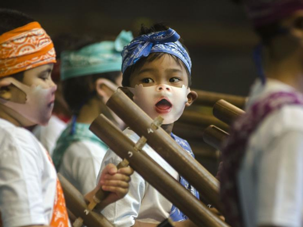Children wearing face mask play traditional music instrument of angklung in Bandung, Indonesia