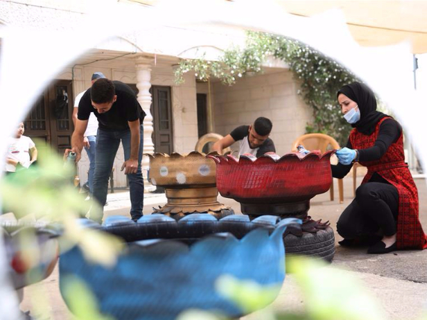 Palestinian woman converts recycled vehicle tires into decorations for home gardens