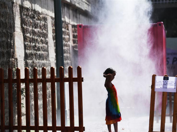 Children cool themselves under steam fountain in Paris, France