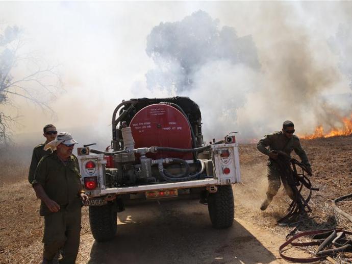 Israeli soldiers extinguish fire near Gaza border