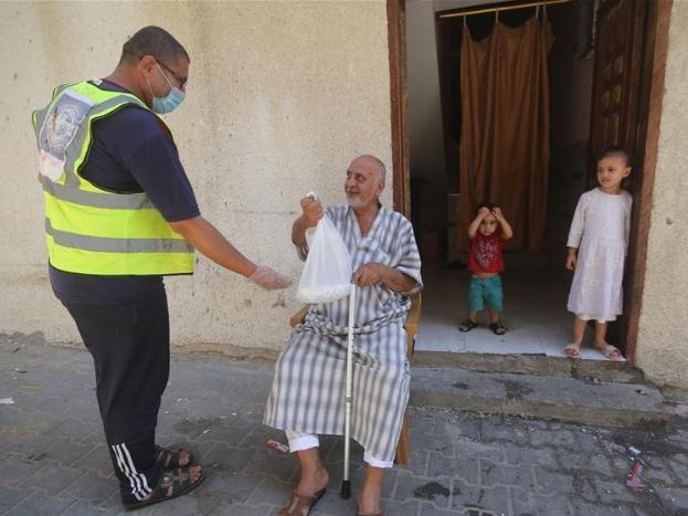 Palestinian volunteers prepare food for people in need during lockdown due to COVID-19 pandemic