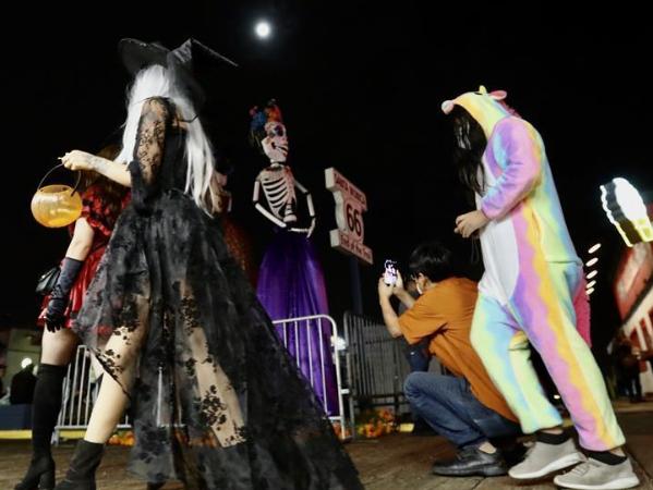 People wearing costumes celebrate Halloween in Los Angeles