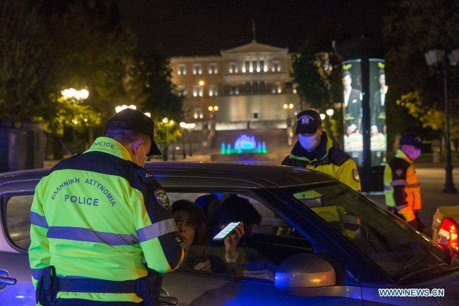Policemen check citizens for permit of movement during curfew in Greece