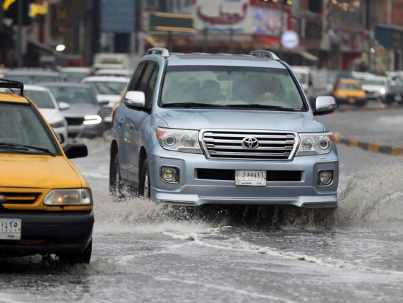 Vehicles run on flooded roads in Baghdad, Iraq