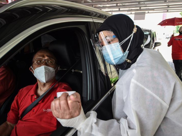 People receive COVID-19 vaccine during drive-thru vaccination campaign in Jakarta