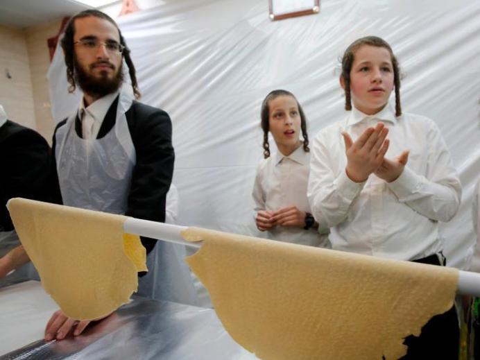 Ultra-Orthodox Jewish men prepare matza for upcoming Jewish holiday of Passover