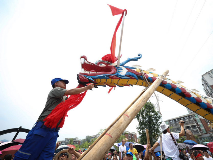 Hundreds of people carry world's largest wooden dragon boat in SW China's Guizhou