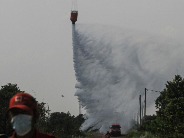 Helicopters dump water on burning peatland in Indonesia