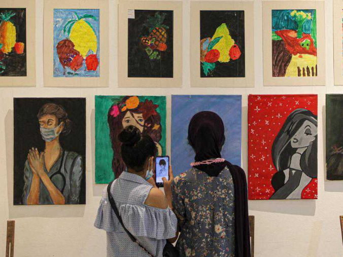 Visitors view artworks made by Palestinian children during exhibition in Gaza City
