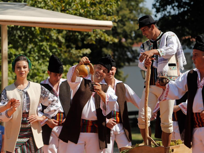 People perform demonstration of ancient wine making at autumn fair in Romania