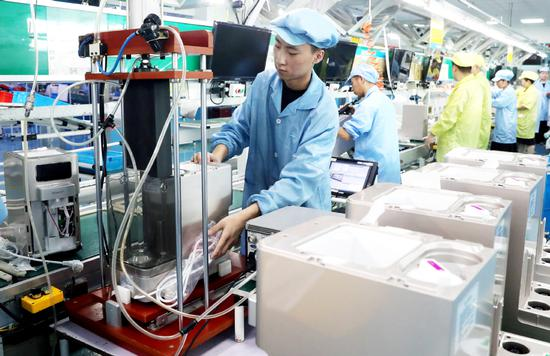 Employees work on the production line of a foreign-funded electronics manufacturer in Suzhou, Jiangsu province. (Photo: China Daily/ Hua Xuegen)