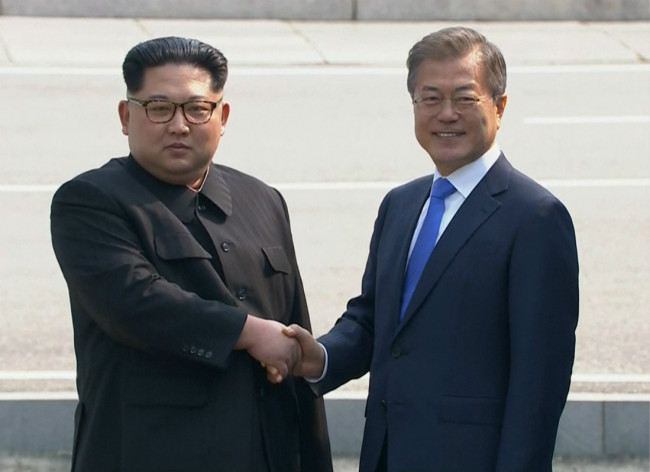 In this image taken from video provided by Korea Broadcasting System, April 27, 2018, North Korean leader Kim Jong Un, left, shakes hands with South Korean President Moon Jae-in as Kim crossed the border into South Korea for their historic face-to-face talks, in Panmunjom. [Photo: AP]