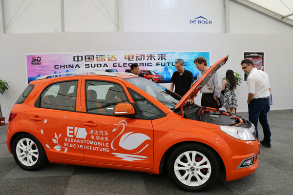 """Visitors take a look at an electric vehicle produced by a Chinese firm displayed on the sidelines of the international cultural and economic exchange event """"Blue Container on the New Silk Road"""" held in Duisberg, North Rhine-Westphalia, Germany. [Photo: China Plus]"""