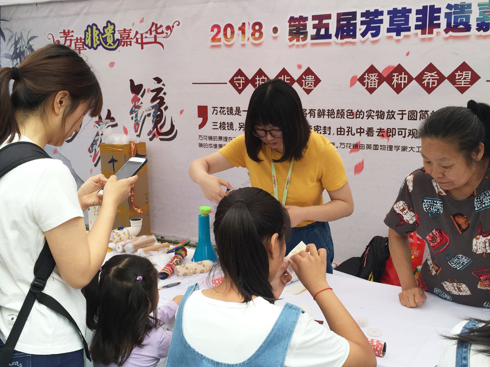 A few visitors to the annual cultural heritage festival in Beijing try to make kaleidoscopes during China's Cultural Heritage Day on Saturday, June 9, 2018. [Photo: China Plus]