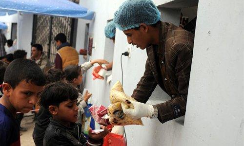 People wait to receive food provided by NGO in Sanaa, Yemen