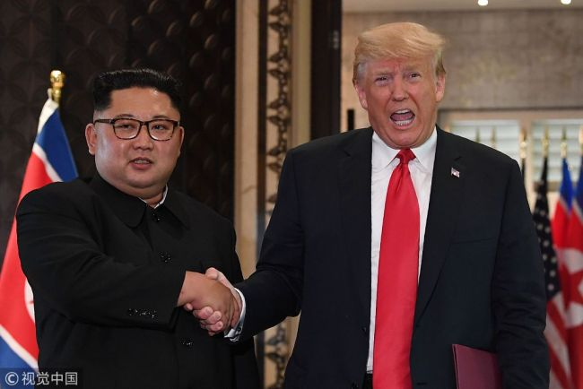 US President Donald Trump (R) and North Korea's leader Kim Jong Un shake hands following a signing ceremony during their historic US-North Korea summit, at the Capella Hotel on Sentosa island in Singapore on June 12, 2018. Donald Trump and Kim Jong Un became on June 12 the first sitting US and North Korean leaders to meet, shake hands and negotiate to end a decades-old nuclear stand-off. [Photo: VCG]