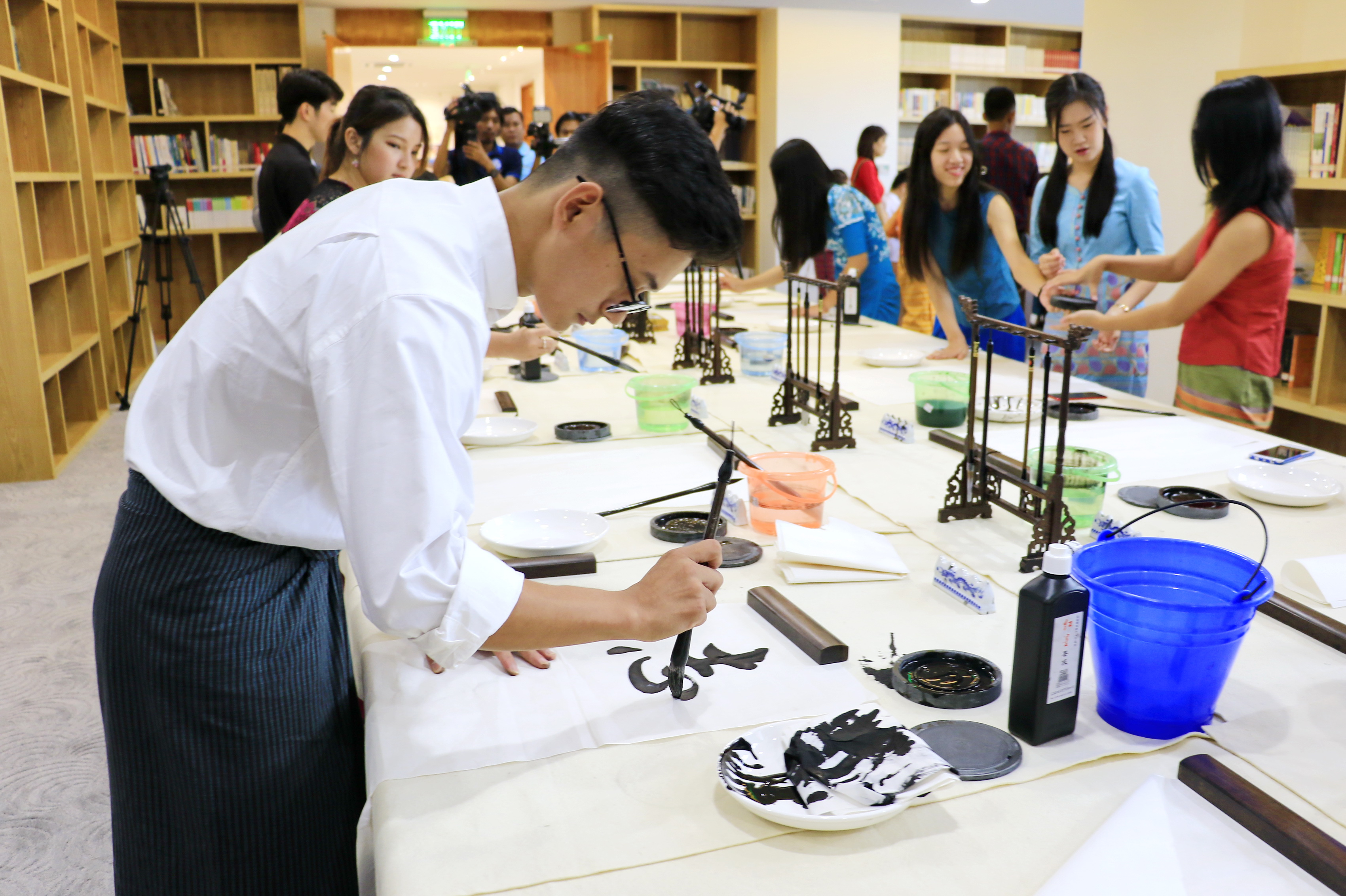A Myanmar practices Chinese calligraphy at the China Cultural Center in Yangon, Myanmar, on July 7, 2018. [Photo: China Plus/Tu Yun]
