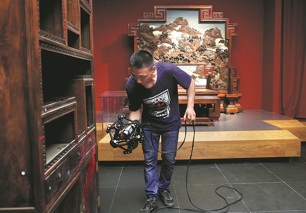 A staff member of the Palace Museum takes measurements of a piece of royal furniture from the Qing Dynasty (1644-1911) on Friday. [Photo: China Daily]