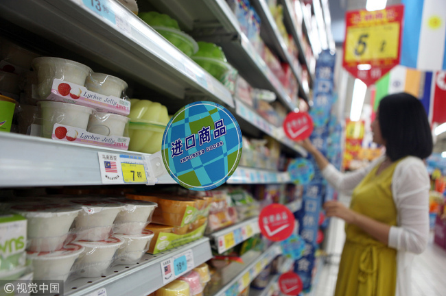 A woman selects imported goods in a supermarket in Rizhao, Shandong Province. [File photo: VCG]