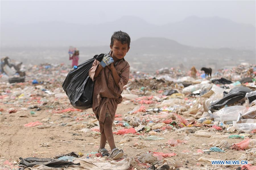 Child carries recyclable items from garbage dump on outskirts of Sanaa, Yemen