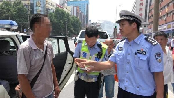 The watermelon vendor is stopped by traffic police officers for breaking the road rules in Zhengzhou, central China's Henan Province, on Saturday, July 14, 2018. [Photo: dahe.cn]