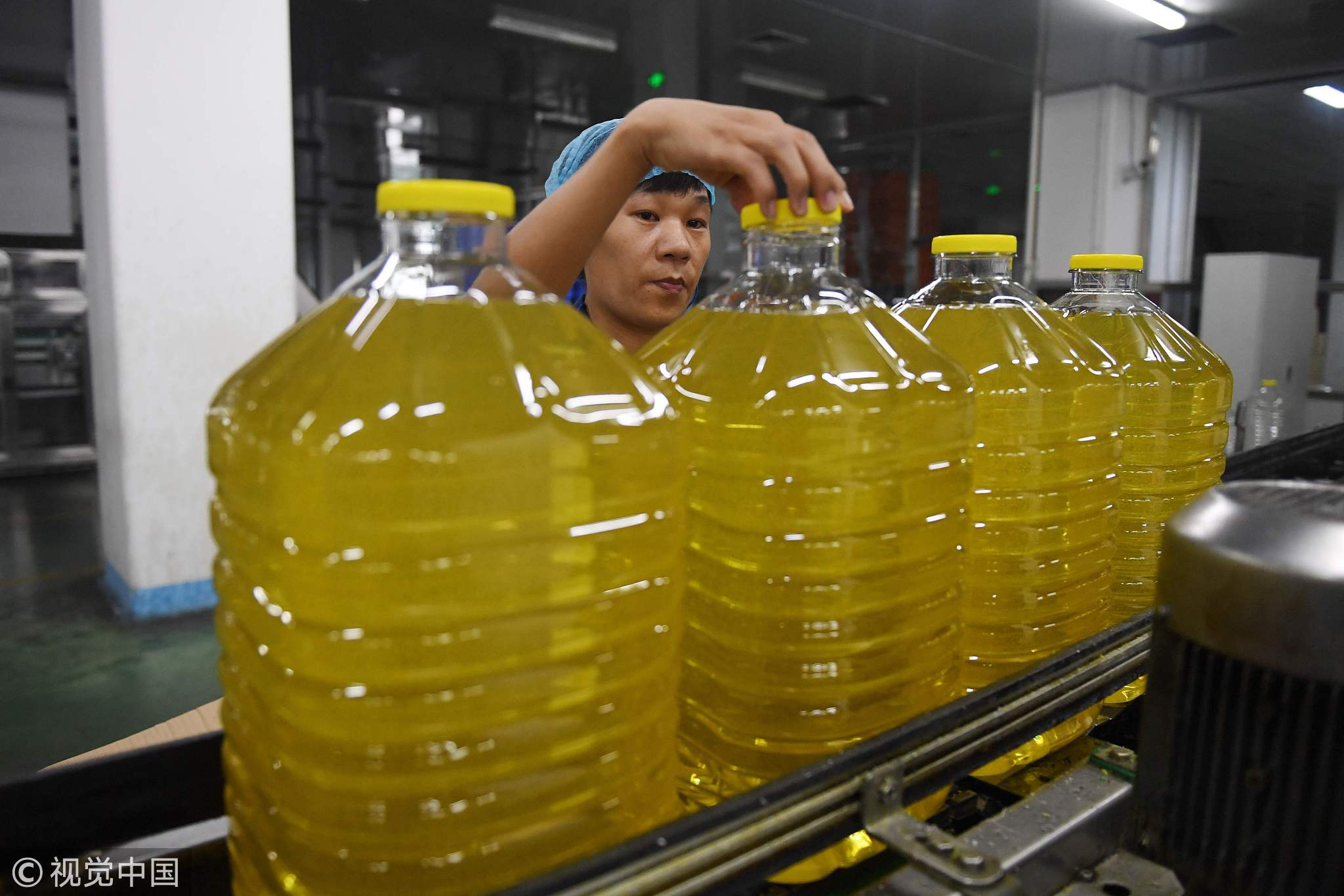 A worker checking a cap on a bottle of soybean oil at the Hopeful Grain and Oil Group factory in Sanhe, in China's northern Hebei province. The company uses soybeans imported from Brazil, after recently changing from a US supplier, July 19, 2018. [Photo: VCG]