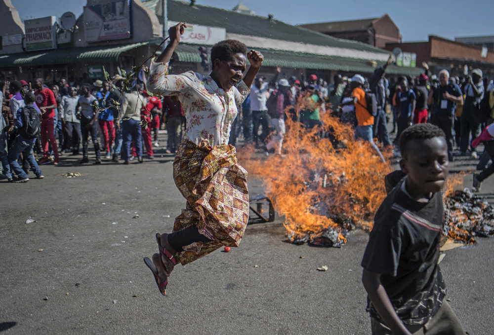 Opposition MDC party supporters protest in the streets of Harare during clashes with police Wednesday, Aug. 1, 2018. [Photo: AP/Mujahid Safodien]