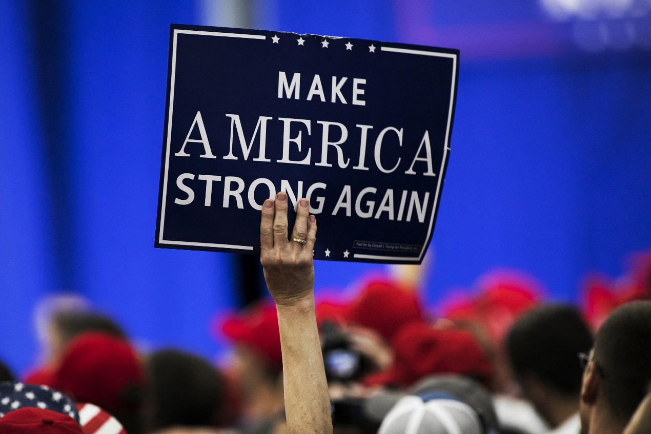 """A person holds slogan at Trump's """"Make America Great Again (MAGA)"""" rally, August 4, 2018. [Photo: VCG]"""