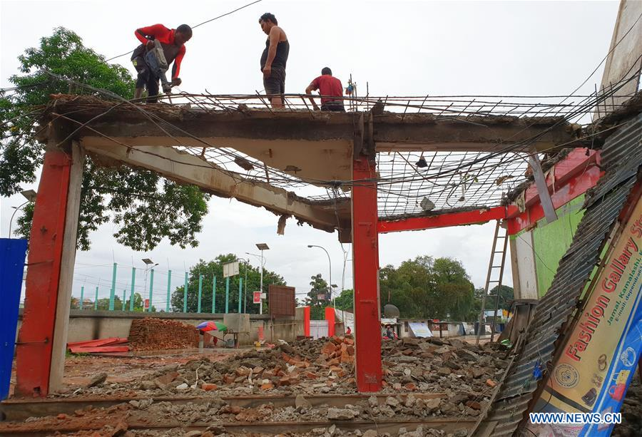 People work at reconstruction site of quake-damaged school in Nepal