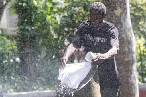 A man uses a park sprinkler to cool off, Wednesday, Aug. 29, 2018, in New York. Dangerously high heat in the Northeastern United States has prompted emergency measures including extra breaks for players wilting at the U.S. Open tennis tournament. [Photo: AP/Mary Altaffer]