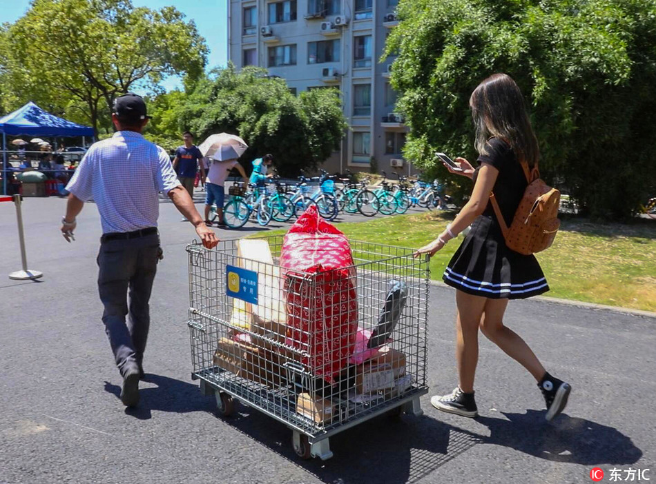 A student uses a trolley to carry her parcels back to the dormitory during the first week of the new semester at Jiangnan University in Wuxi City, Jiangsu Province on August 29, 2018. [Photo: IC]