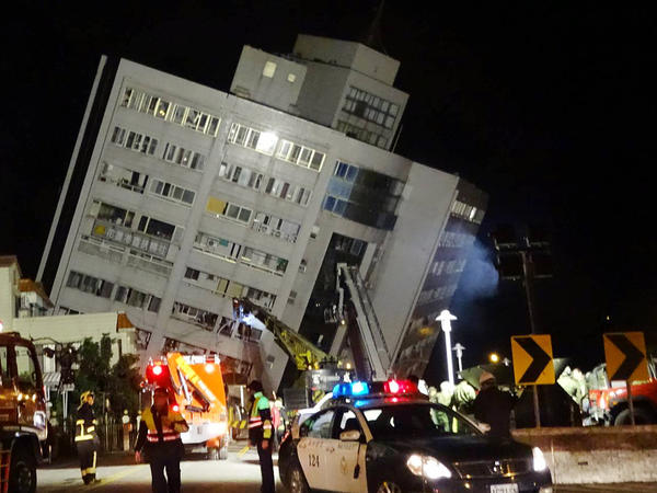 Rescuers are seen entering a building that collapsed onto its side from an early morning 6.4 magnitude earthquake in Hualien County, eastern Taiwan, Wednesday, Feb. 7 2018.