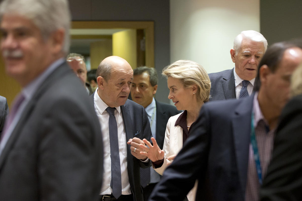 French Foreign Minister Jean-Yves Le Drian, center left, speaks with German Defense Minister Ursula von der Leyen, center right, during a meeting of EU foreign and defense ministers at the Europa building in Brussels, Monday, Nov. 13, 2017. The European Union is banning arms sales to Venezuela and setting up a system for asset freezes and travel restrictions on some Venezuelan officials to ramp up pressure on President Nicolas Maduro. (AP Photo/Virginia Mayo)