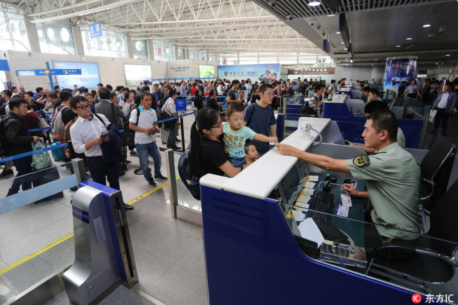 A family traveling overseas go through customs clearance at a border inspection post at an airport. [File photo: IC]