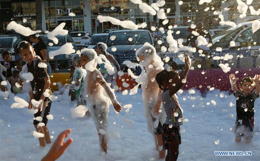 Israeli children play in pool of soap bubbles during summer vacation
