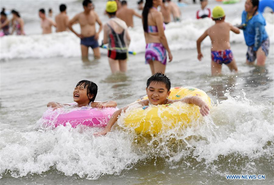 People play with water on beach in Beihai, S China's Guangxi
