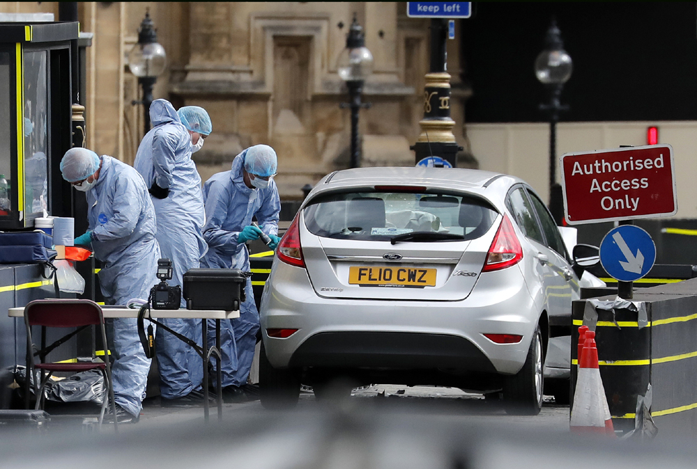 Forensics officers work near the car that crashed into security barriers outside the Houses of Parliament in London, Tuesday, Aug. 14, 2018.[Photo: AP/Frank Augstein]