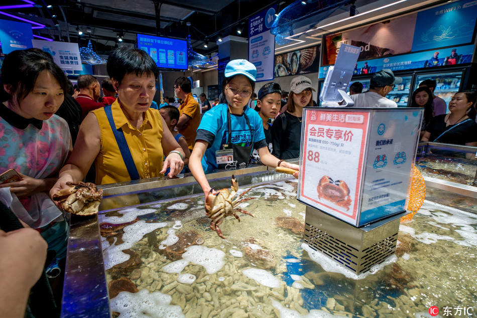 Customers shop at a store of O2O fresh produce retailer Hemaxiansheng, also known as Hema Fresh Store, of Chinese e-commerce giant Alibaba Group in Guangzhou city, south China's Guangdong province, 29 July 2018. [Photo:IC]