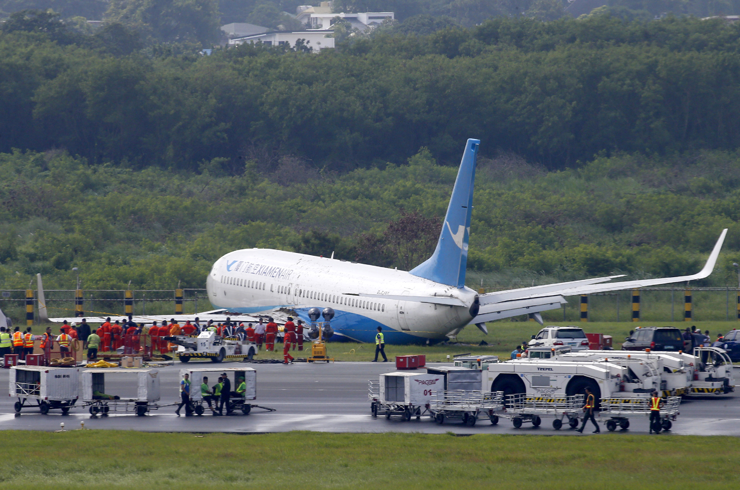 A Boeing passenger plane from China, a Xiamen Air, sits on the grassy portion of the runway of the Ninoy Aquino International Airport after it skidded off the runway while landing Friday, Aug. 17, 2018 in suburban Pasay city southeast of Manila, Philippines. All the passengers and crew of Xiamen Air Flight 8667 were safe and were taken to an airport terminal, where they were given blankets and food before being taken to a hotel. [Photo: AP/Bullit Marquez]