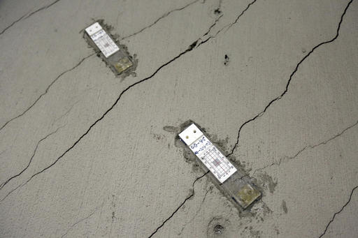 FILE - In this photo taken Monday, Oct. 3, 2016, stress gauges are placed along a wall with floor-to-ceiling cracks in the parking garage of the Millennium Tower in San Francisco. The 58-story tower has gained notoriety as the leaning tower of San Francisco. It's not just leaning. It's sinking, too. And engineers hired to assess the problem say it shows no immediate sign of stopping. The sleek, mirrored high-rise that opened in 2009 as a haven for the city's well-heeled has sunk 16 inches and is leaning at least 2 inches toward other skyscrapers in the crowded downtown financial district. [Photo: AP/Eric Risberg]