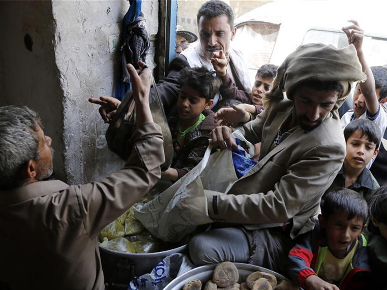 Yemenis receive food from food distribution center in Sanaa