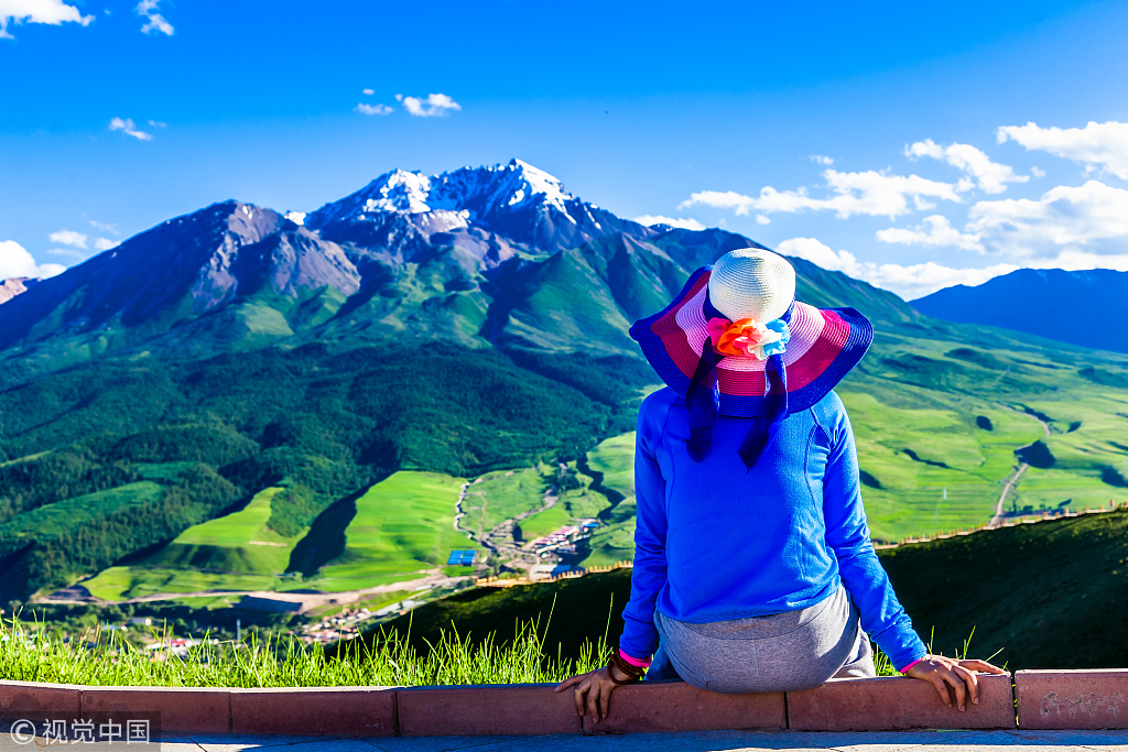 A visitor is looking at the Qilian Mountain. [File Photo: VCG]