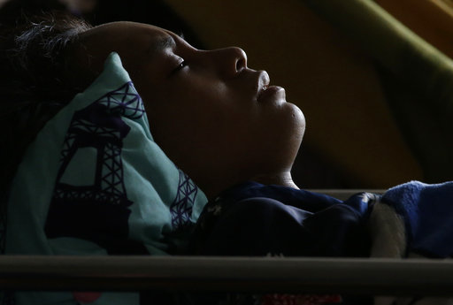 Anisa Cornelia grimaces in pain as she lies inside a medical tent after being injured in a massive earthquake and tsunami in Palu, Central Sulawesi, Indonesia Thursday, Oct. 4, 2018. [Photo: AP]