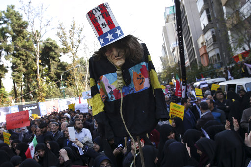 """An effigy of U.S. government icon """"Uncle Sam"""" is held up by demonstrators during a rally in front of the former U.S. Embassy in Tehran, Iran, on Sunday, Nov. 4, 2018, marking the 39th anniversary of the seizure of the embassy by militant Iranian students. Thousands of Iranians rallied in Tehran on Sunday to mark the anniversary as Washington restored all sanctions lifted under the nuclear deal. [Photo: AP]"""