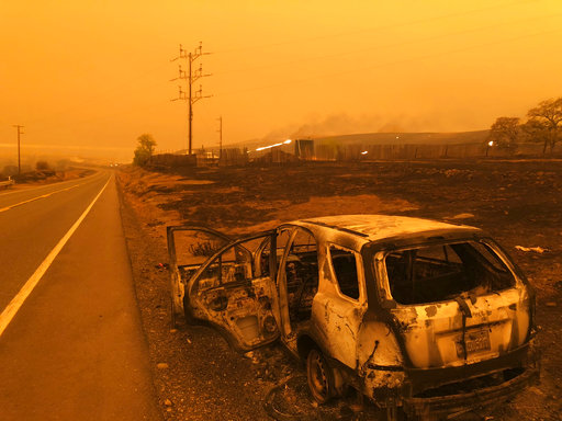 A burned out car sits on the side of the road in Paradise, Calif., Friday, Nov. 9, 2018, after a wildfire swept through the area. [Photo:AP]