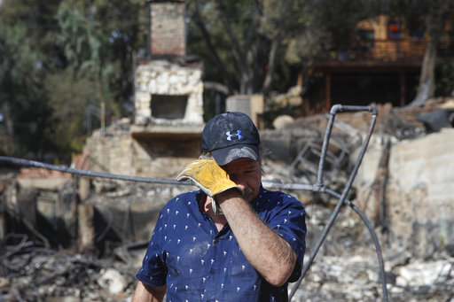 Roger Kelton, 67, wipes his tears while searching through the remains of his mother-in-law's home burned down by the Woolsey Fire Tuesday, Nov. 13, 2018, in Agoura Hills, Calif. [Photo: AP]