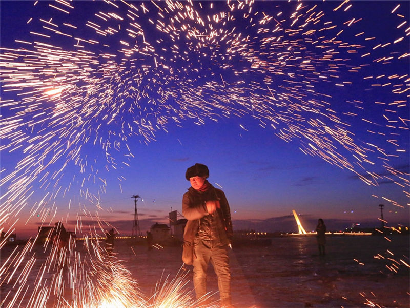 Handheld fireworks illuminate a frozen river in N.E. China
